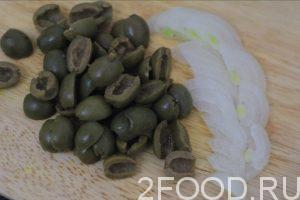 Нарезаем оливки пополам. Лук режем тонкими полукольцами